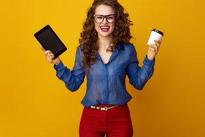 happy woman isolated on yellow showing coffee cup and tablet PC