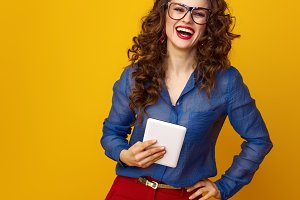 smiling young woman against yellow background with tablet PC