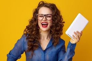 cheerful woman isolated on yellow background with tablet PC