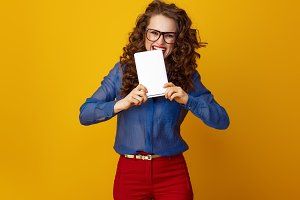 smiling woman biting tablet PC isolated on yellow background