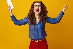 happy woman against yellow background with tablet PC rejoicing