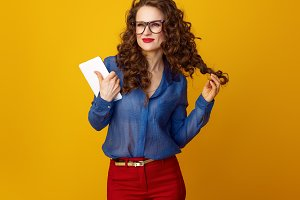 happy stylish woman on yellow background looking into distance