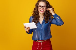 smiling woman with tablet PC listening to music with headphones