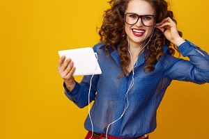 happy woman with tablet PC and headphones listening to music