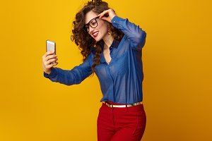 woman against yellow background taking selfie with cellphone