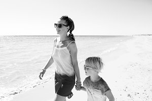 smiling trendy mother and daughter on seashore walking