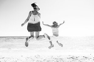 trendy mother and daughter on seacoast jumping
