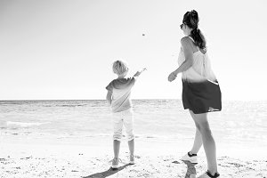 trendy mother and daughter on seashore throwing stones