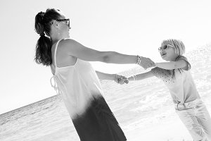 happy modern mother and daughter on beach having fun time