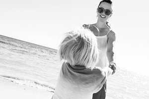 happy modern mother and child on seashore having fun time