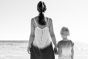 trendy mother and daughter on seashore looking into distance