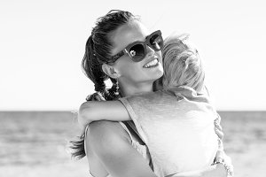 happy modern mother and daughter on beach hugging