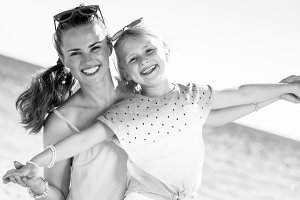 smiling trendy mother and daughter on seashore having fun time