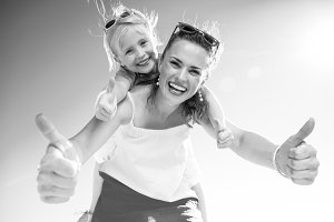 smiling trendy mother and child on beach showing thumbs up