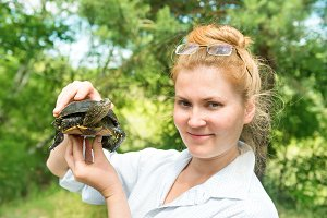 Woman in glasses holding pet turtle