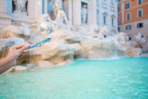 Small toy plane on background of Fountain of Trevi in Rome.