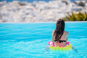Young beautiful woman enjoying summer vacation in outdoor swimming pool