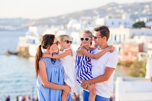 Parents and kids on Little Venice background on Mykonos Island, in Greece