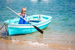 Little girl in blue boat in the sea bay in Greece