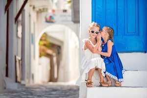 Little happy girls in dresses at street of typical greek traditional village on Mykonos Island, in Greece