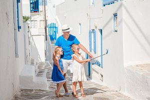 Father and kids taking selfie background Mykonos town in Greece