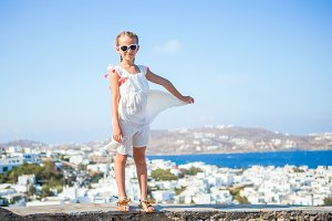Little girl in european town outdoors on Mykonos island