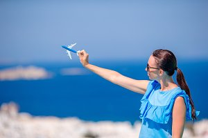 Tourist woman with toy airplane in hands background the old greek village