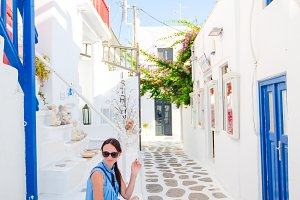 Caucasian tourist walking along the deserted streets of greek village.
