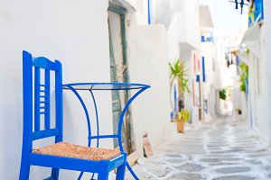 The narrow streets with blue balconies, stairs, white houses and flowers in beautiful village in Greece.