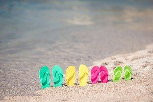 Family colorful flip flops on beach in front of the sea