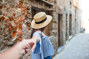 Boyfriend following girlfriend holding hands in old european street laughing and smiling