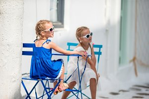 Two girls in blue dresses having fun outdoors on Mykonos streets