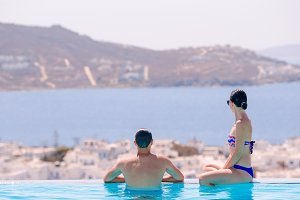 Happy young romantic couple relaxing on the edge of swimming pool