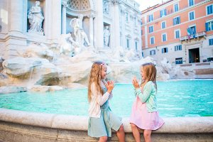 Adorable little girls on the edge of Fountain of Trevi in Rome.