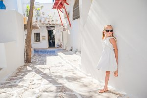 Adorable little girl at old street of typical greek traditional village