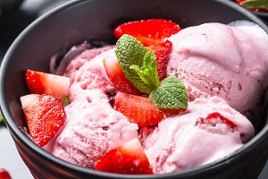 Strawberry ice cream with fresh berries on black.