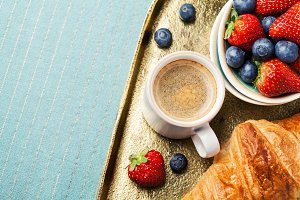 Breakfast setting with coffee, berries  and croissant, shallow DOF