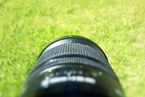 Photography lens pointed on fresh green summer grass background
