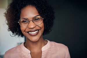 African businesswoman standing in a modern office smiling confidently
