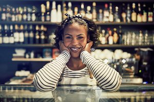 Smiling African entrepreneur standing in her trendy cafe