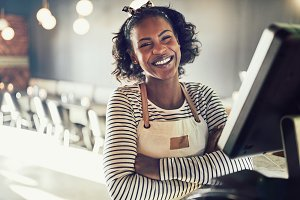 Young African waitress laughing while working in a trendy restaurant