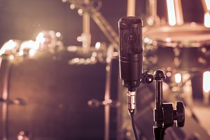 The microphone in a recording Studio or a concert hall close up of drum kit and an acoustic guitar in the background.