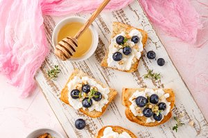 Toast with fresh berries blueberry Ricotta cheese, thyme, honey and hazelnuts, served