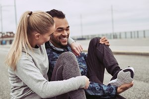 Young couple laughing while taking a break from jogging