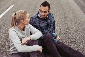 Young couple smiling while sitting on a road after jogging