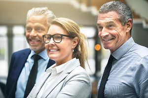 Smiling mature businesspeople standing together in an office lobby