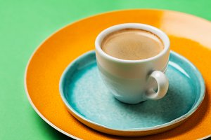 Cup of coffee on colorful tableware and bright background