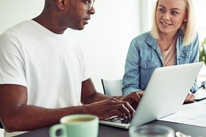 Two diverse office colleagues using a laptop and talking together