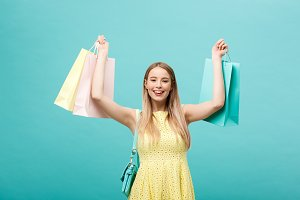 Lifestyle Concept: Portrait of shocked young attractive woman in yellow summer dressposing with shopping bags and looking at camera over blue background.