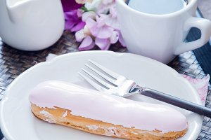 Rose eclair and coffee cup
